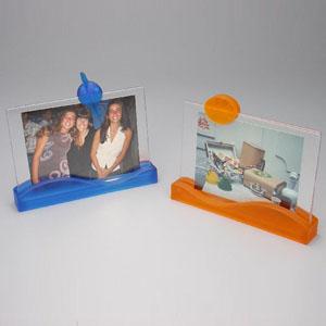 brindes-da-terra - Porta retrato para foto 10x15, modelo ondinha, material PS jateado em várias cores com 02 visores PS cristal e boton.  Gravação em silk screen.