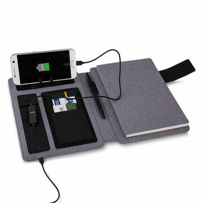 Fabricada em poliuretano e poliester, na cor cinza ou preto, a pasta power bank personalizada con...