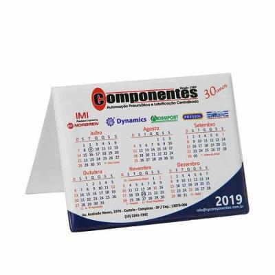 Calendário de mesa confeccionado em PVC e acabamento em solda eletrônica. Impressão em silk-screen.