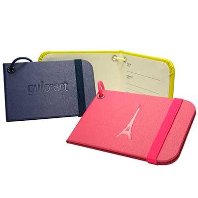 - Tag de mala/Identificador de bagagem, elástico para fechamento, revestimento em couro sintético, personalização baixo relevo, logotipo interno.