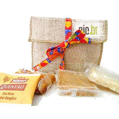 Kits & Requintes - Necessaire de Juta personalizada, com 1 cocada 51g, 1 doce de leite chup chup 30g, 1 pé de moleque 20g e 1 chá de quentão. Fechamento com fita colorid...
