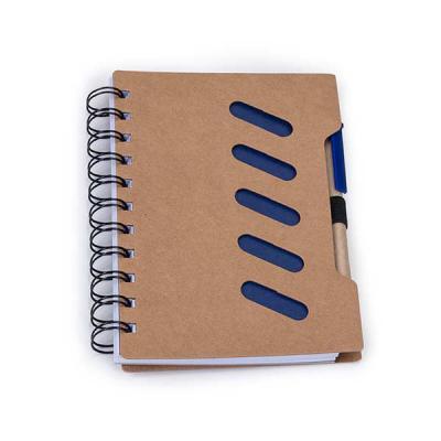 Bloco de anotações ecológico com caneta reciclada. Possui cinco detalhes vazados na capa e verso liso, espiral preto,suporte elástico com caneta de pa... - SOMA Brindes