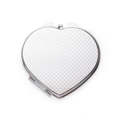 SOMA Brindes - Espelho de metal duplo em formato coração com aumento. Frente lisa espelhada e verso texturizado.  Tamanho total aproximado (CxD): 7cm x 7,1 cm  Peso...