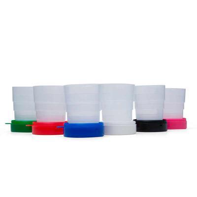 """- Copo Retrátil  de plástico com tampa porta comprimido e base colorida. Basta puxar para cima para """"armar"""" o copo, possui """"suporte"""" para chaveiro. Na á..."""