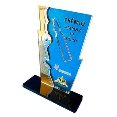 AD Plastic - Troféu constituído por uma placa de 10mm, em acrílico cristal, com placas sobrepostas nas laterais em acrílico dourado e prata espelhado