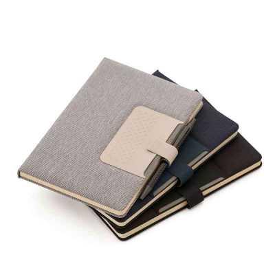 Caderno de anotações com suporte para caneta, fechamento magnética, capa dura em material sintético, miolo 80 folhas pautadas na cor bege. Dimensão do... - Crazy Ideas
