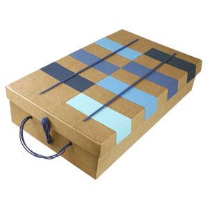 Crazy Ideas - Embalagem personalizada em kraft, com retângulos em collor plus azul de vários tons, com tampa articulada e fechamento com alça em cordão.